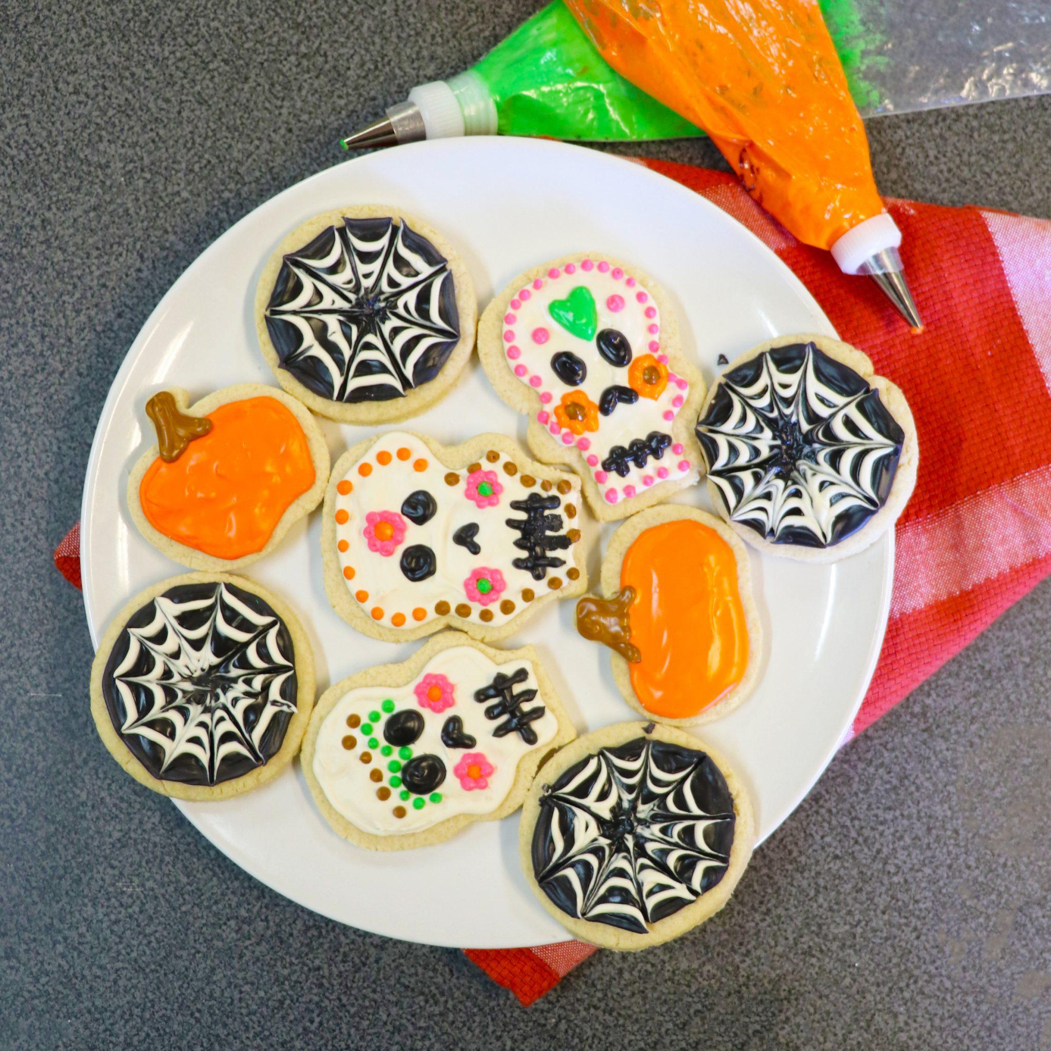 picture of sugar skull, pumpkin, and spider web cookies made for Día de los Muertos