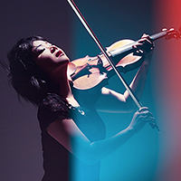woman plays the violin in dramatic lighting